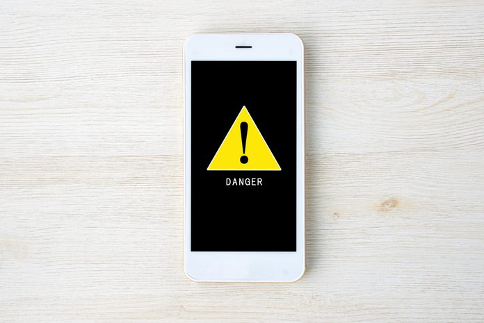 apple iphone virus warning; overhead view of a smartphone on a light wood background with an alert symbol on the screen