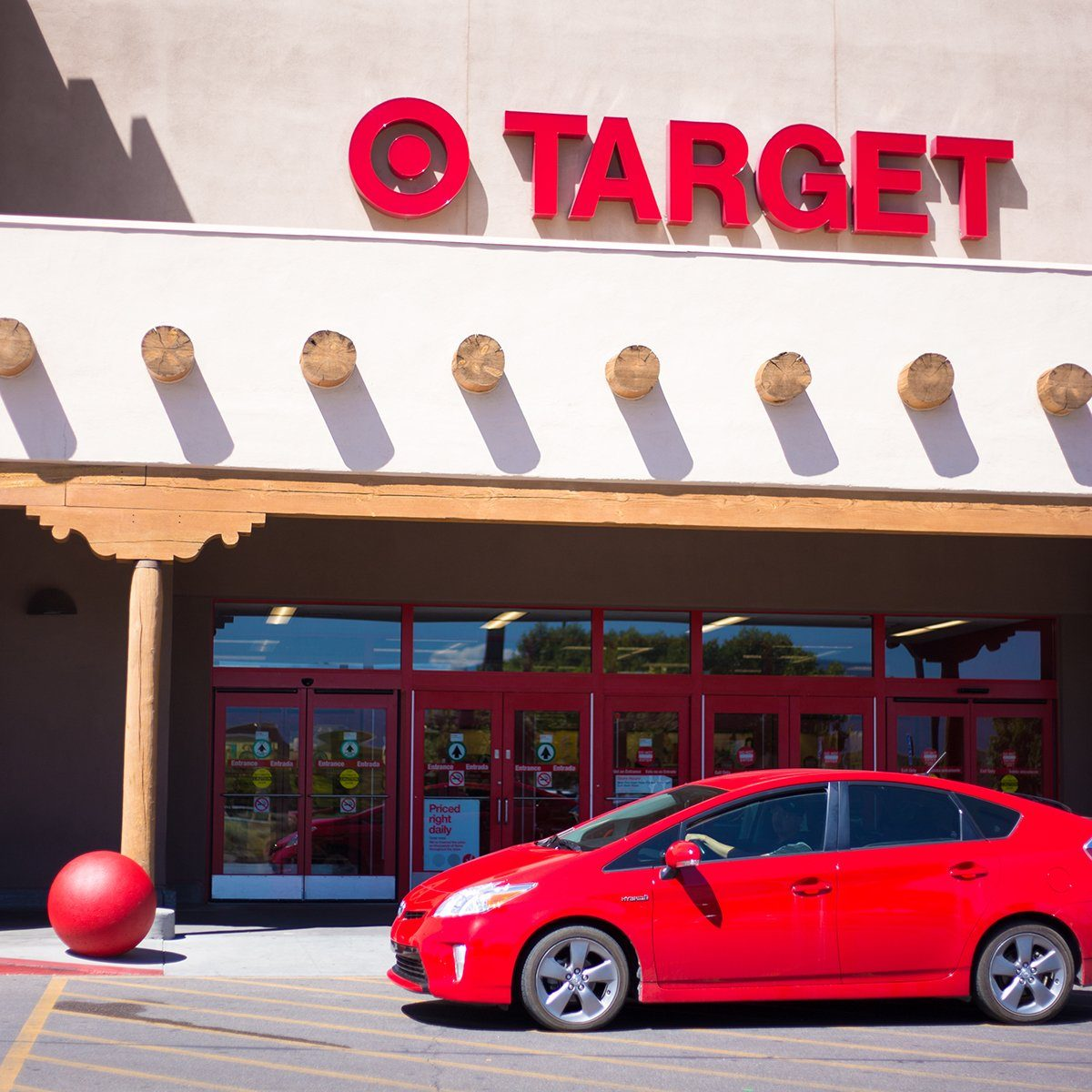 Santa Fe, NM: A red car drives past the entrance to Target, which is constructed in the Southwest Pueblo architectural style.