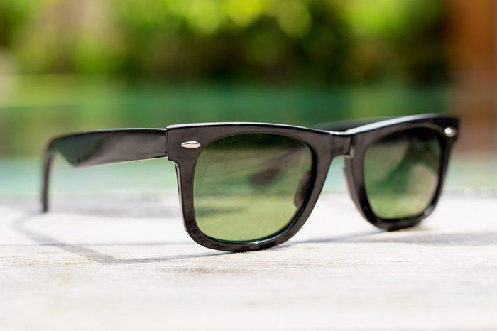 Black sunglasses next to swimming pool
