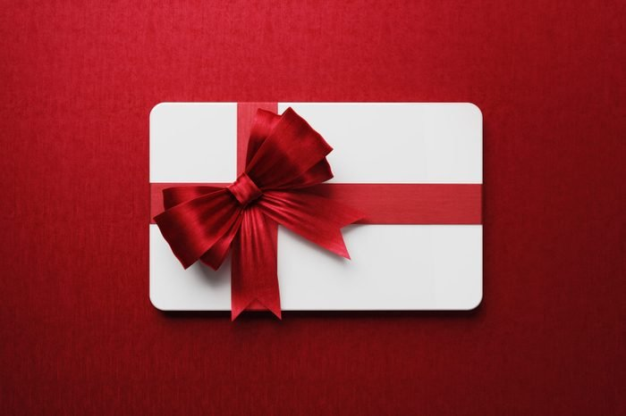 White Gift Card With Red Bow Tie On Red Background