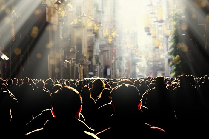 crowd of silhouetted people walking on busy street