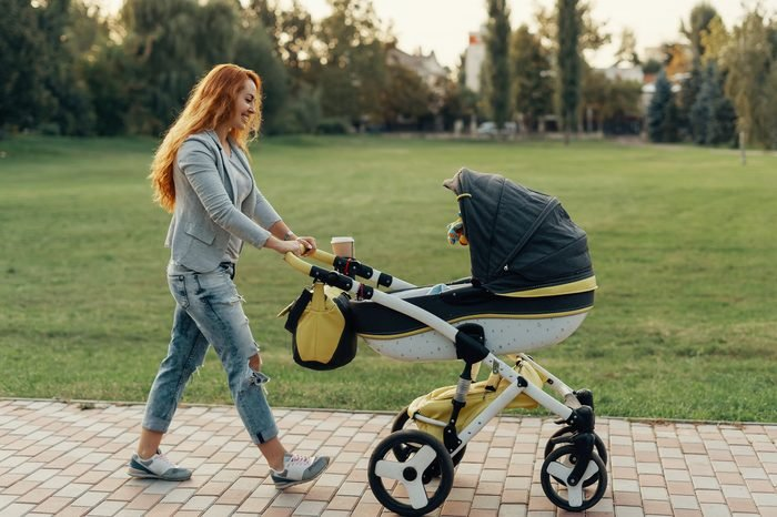 Mother enjoying walk carrying her little child in his baby trolley.