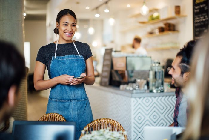 Beautiful waitress at cafe taking order from customers