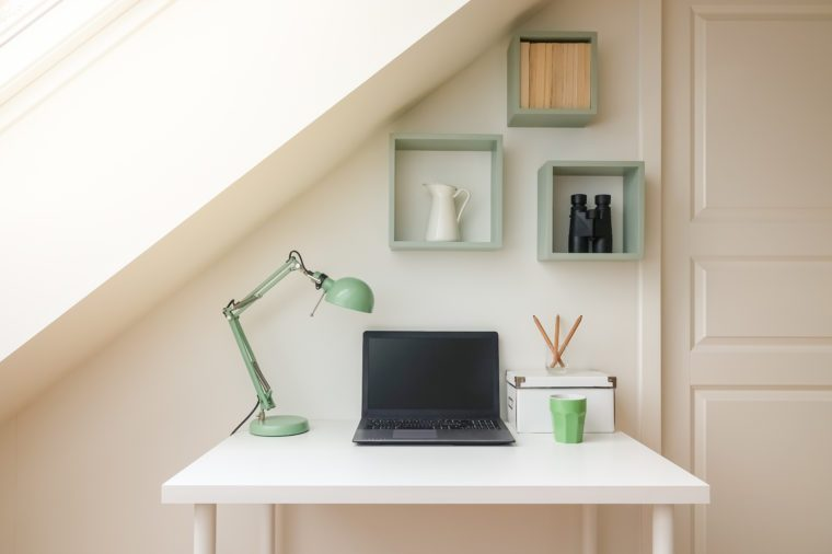 Modern workspace interior in cozy attic / loft apartment with skylight window letting the sun shine in.
