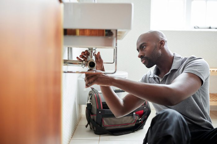 plumber working on the sink in a bathroom
