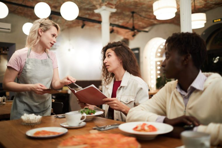 Disgruntled curly-haired young female restaurant guest sitting at table with boyfriend and reading menu while talking to waitress giving advice to her in modern loft cafe