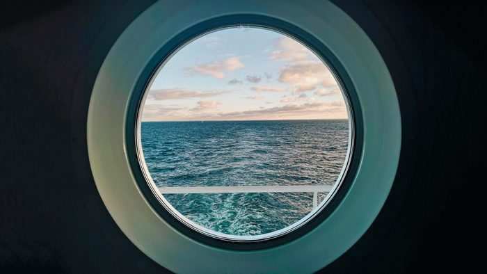 porthole window on a cruis ship looking out onto ocean water