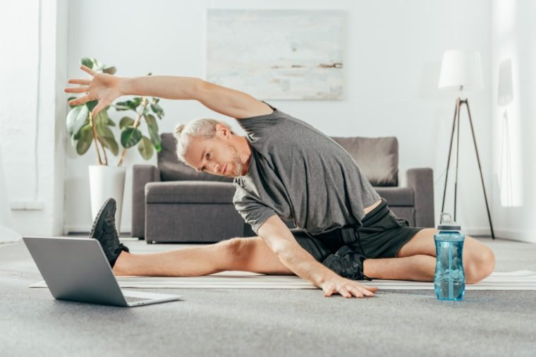 sporty adult man stretching on yoga mat and looking at laptop