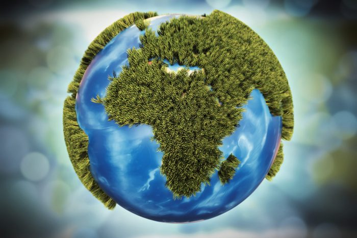 Stylized Earth globe with cartoony grass isolated on bokeh background