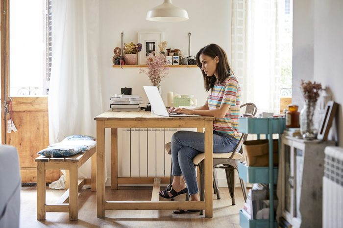 Mid adult woman using laptop at table in kitchen