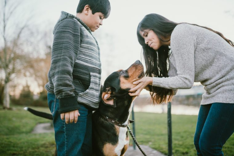 Hispanic Mother And Son Pet Their Dog