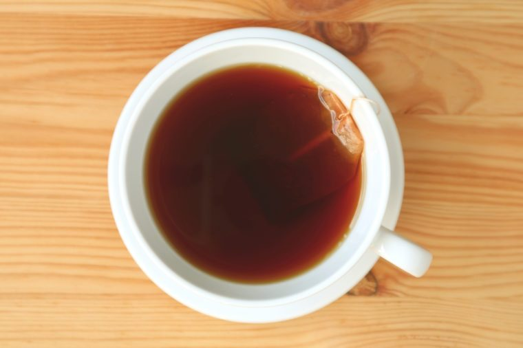 Top view of freshly brewed hot tea with tea bag served on wooden table