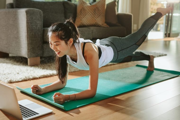 Woman watching sports training online on laptop.