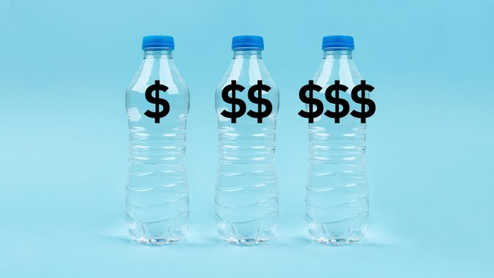 """three plastic water bottles with """"$"""" """"$$"""" and """"$$$"""" on blue background"""