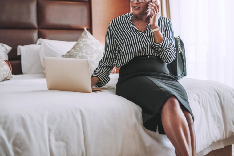 woman in modern hotel room sitting on bed using laptop and talking over mobile phone. Business woman in hotel room using laptop and smartphone.