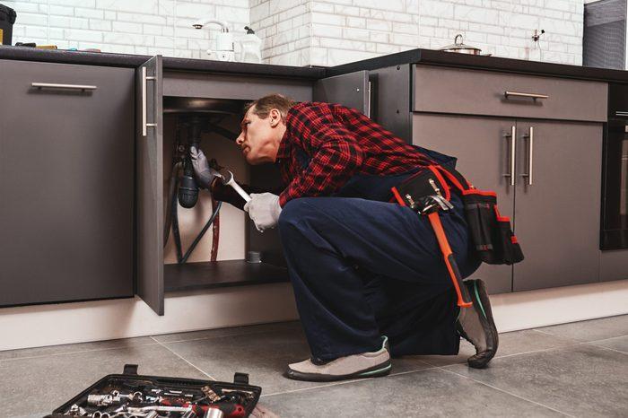 Fitting repair with wrench. Seniour handyman repairing washbasin