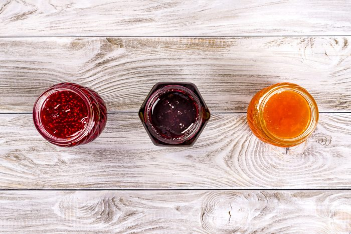Three bowls with different jams on wooden table. Top view