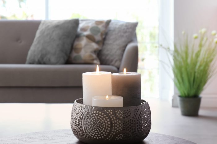 Vase with burning candles on table in living room