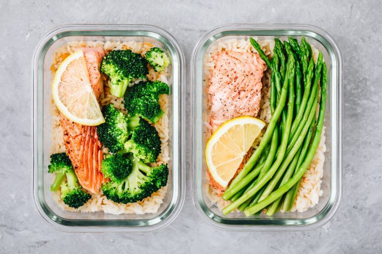 Meal prep lunch box containers with baked salmon fish, rice, green broccoli and asparagus