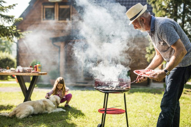 Mature man preparing barbecue for his grandkid in the backyard. Focus is on man.