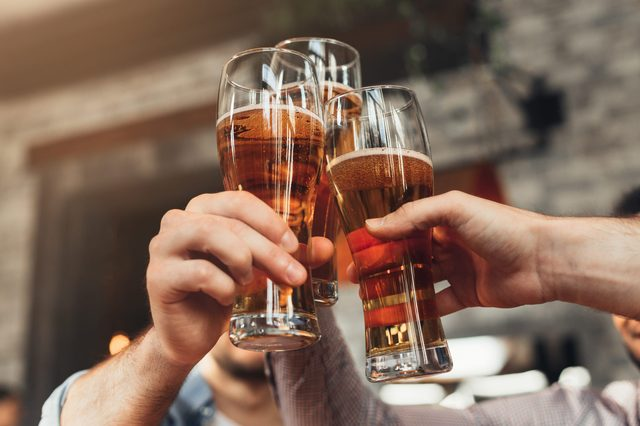 Friends toasting with glasses of beer at the pub