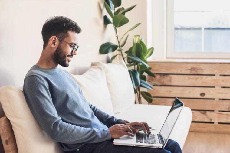 Cheerful man using laptop at home