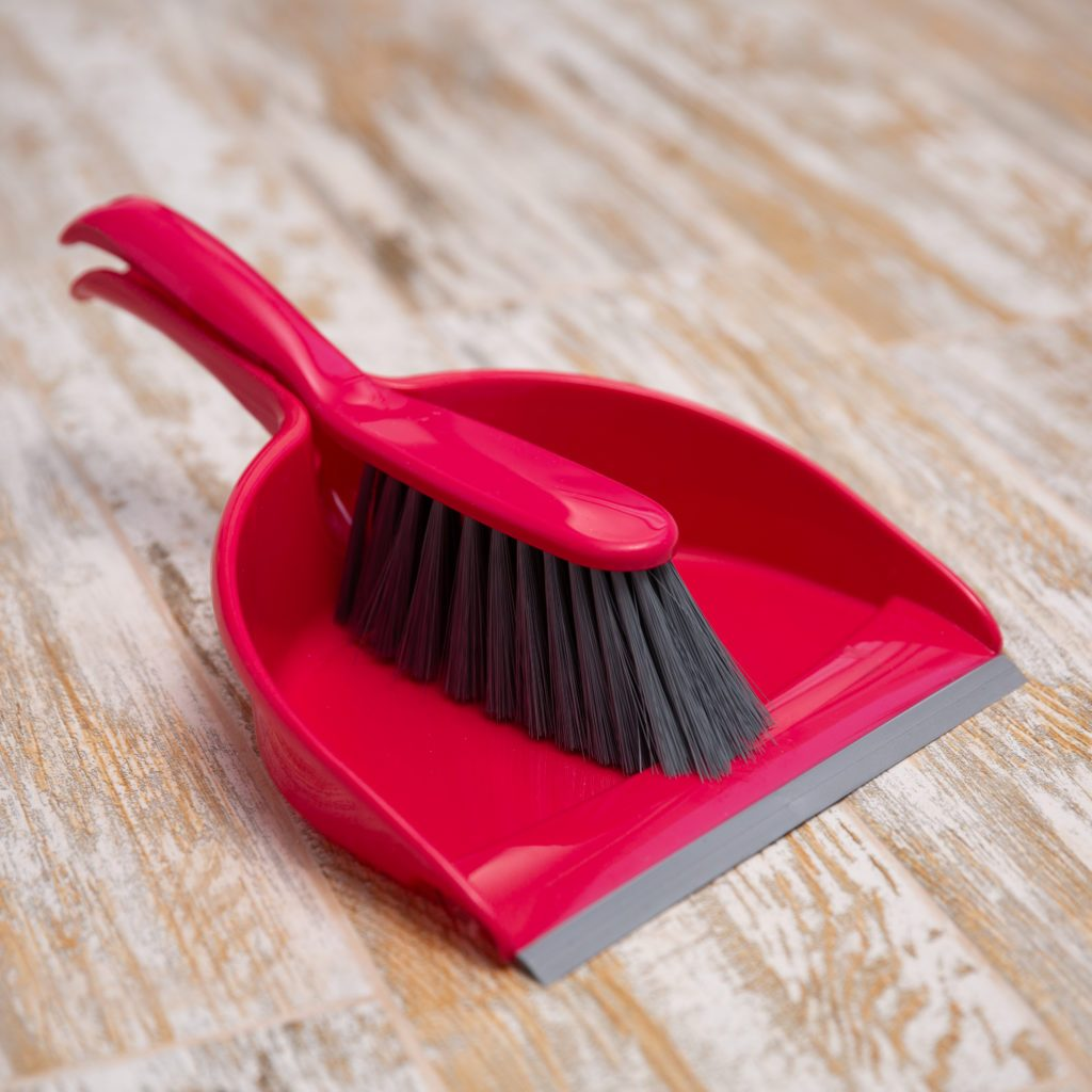 Broom and scoop on wooden background. Plastic equipment for cleaning