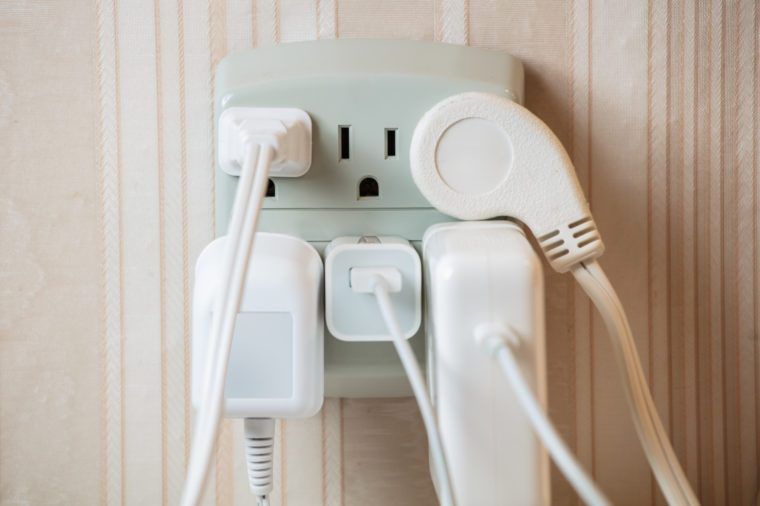 Electrical socket overloaded on wall. Electric wires plugged into socket