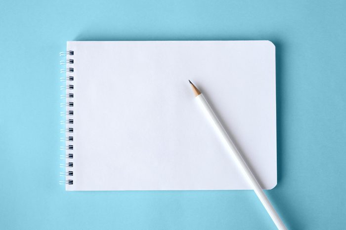 notepad and white pencil on blue background