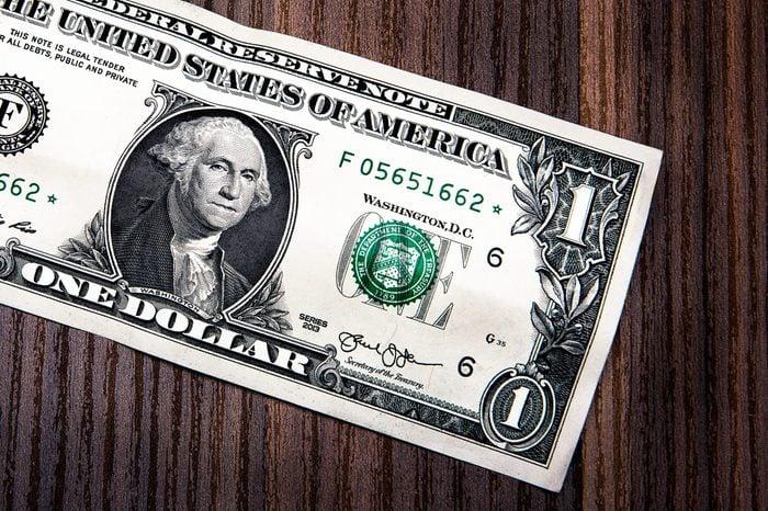 dollar bill on wooden desk close up