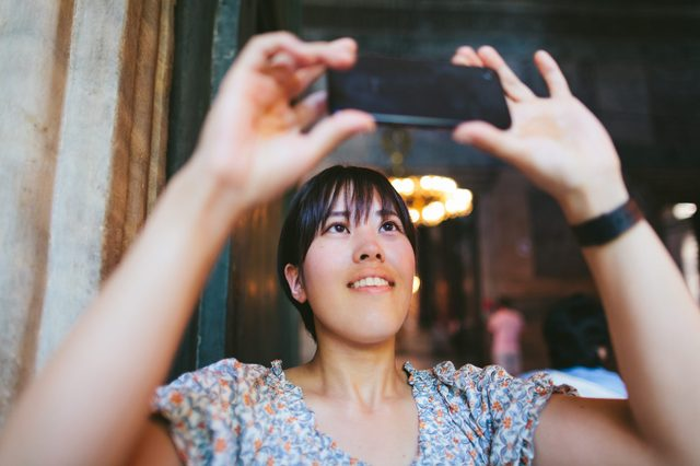 Young female solo traveler taking photos with smart phone