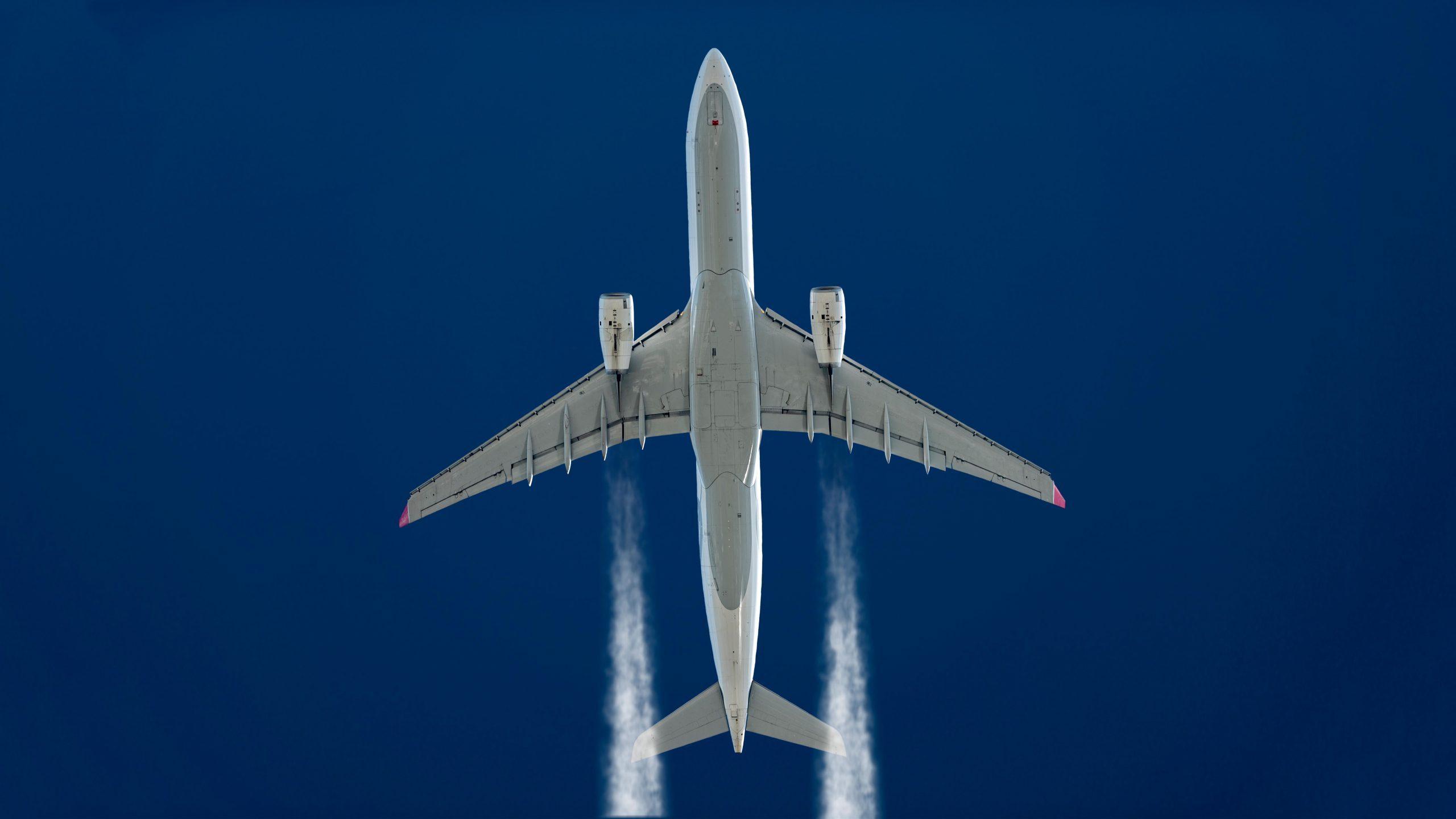 underside of a plane flying. blue sky background. vapor trails.