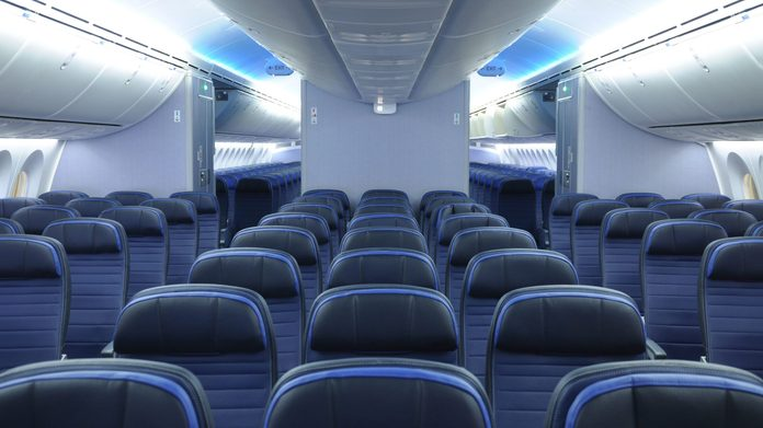 787 dreamliner commercial airplane cabin interior with blue leather seats