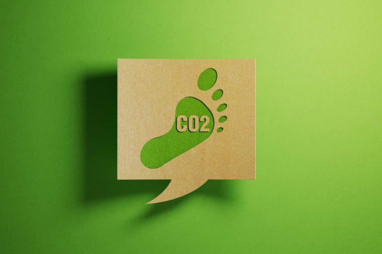 Carbon Footprint Icon on A Chat Bubble Which Is Made of Recycled Paper Over Green Background