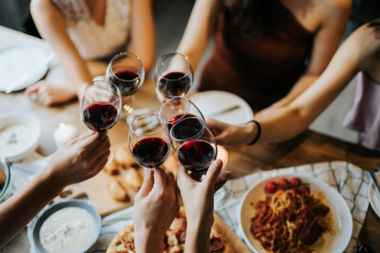Close up of happy young friends having fun and toasting and celebrating with red wine during party