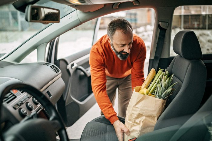 man placing paper bag full of groceries on the passenger side front seat