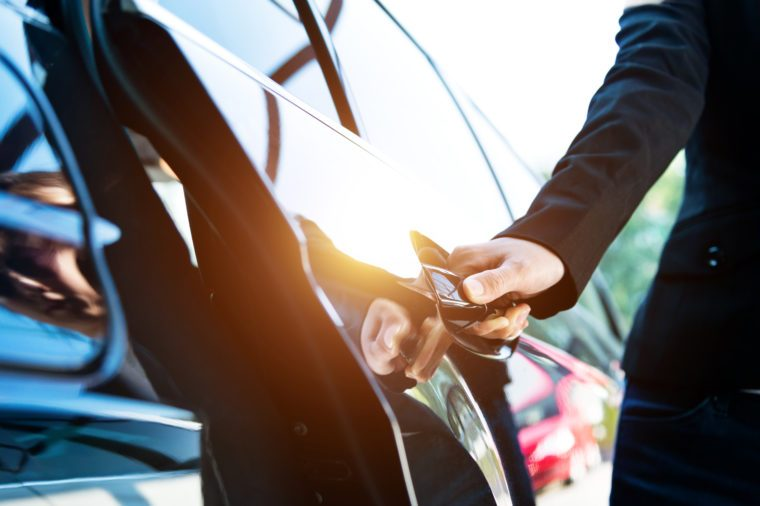 Female chauffeur opening a luxury car door.