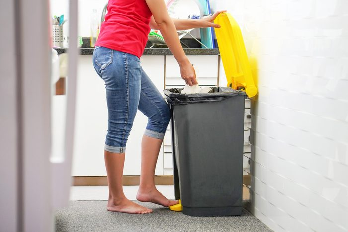 A woman throws garbage in the trash in the kitchen.