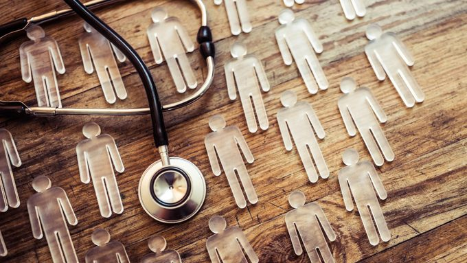 epidemic medicine concept- many transparent figurines and stethoscope on wood background