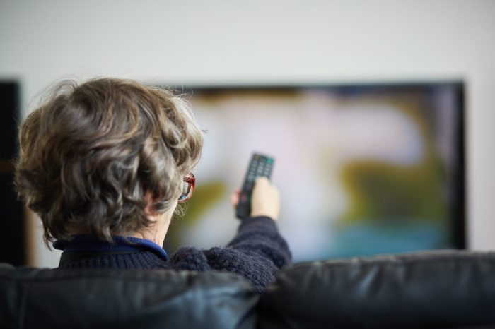 Senior woman with remote control changing channels on her TV