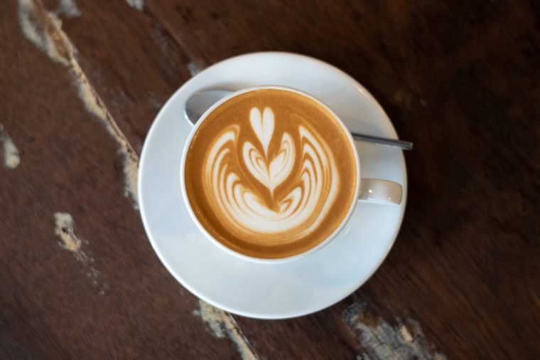 Delicious flat white coffee with latte art in white cup on top of a wooden table