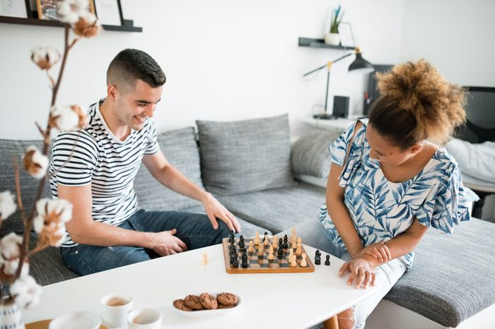 Young heterosexual couple sitting in the living room and playing chess