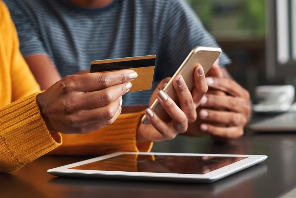 Woman in cafe holding credit card and mobile phone