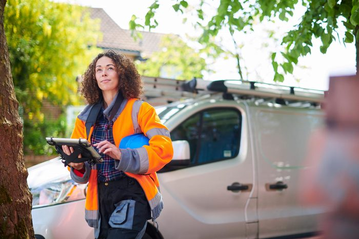 woman in an orange work coat with a tablet near a white utility van
