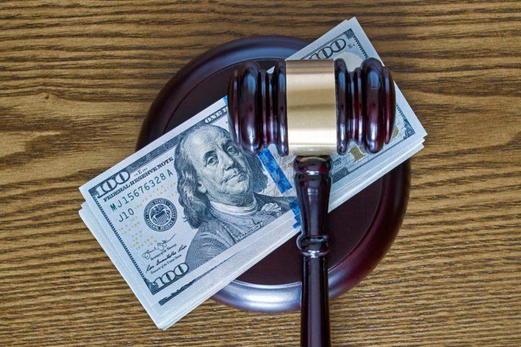 Judge gavel and stack of 100 dollar bills on wooden desktop