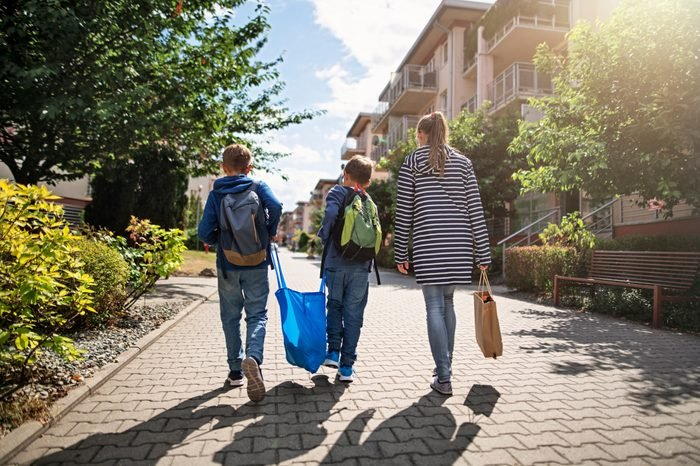 Three kids carrying shopping home in resusable shopping bags