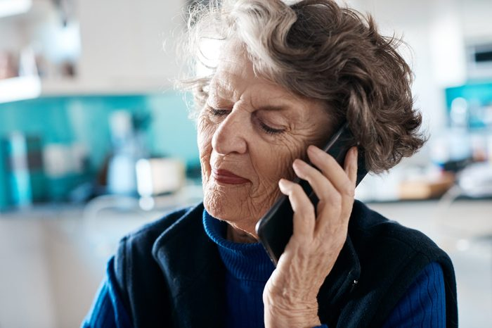 Smiling senior woman talking on mobile phone at home