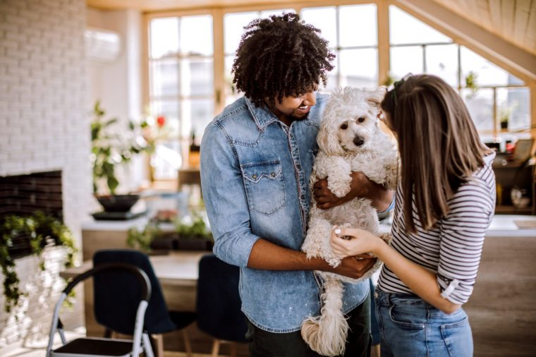 Multi-ethnic couple at home with their cute dog