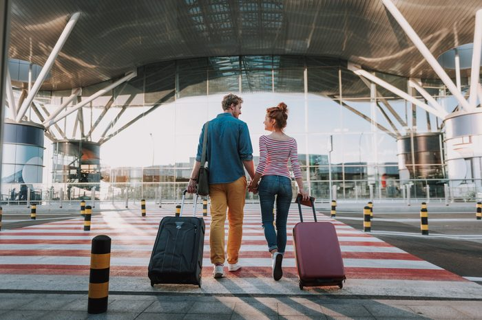Beautiful loving couple with travel suitcases holding hands in airport