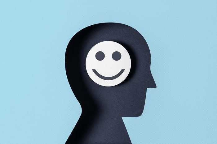 head paper silhouette with smiling face in the brain
